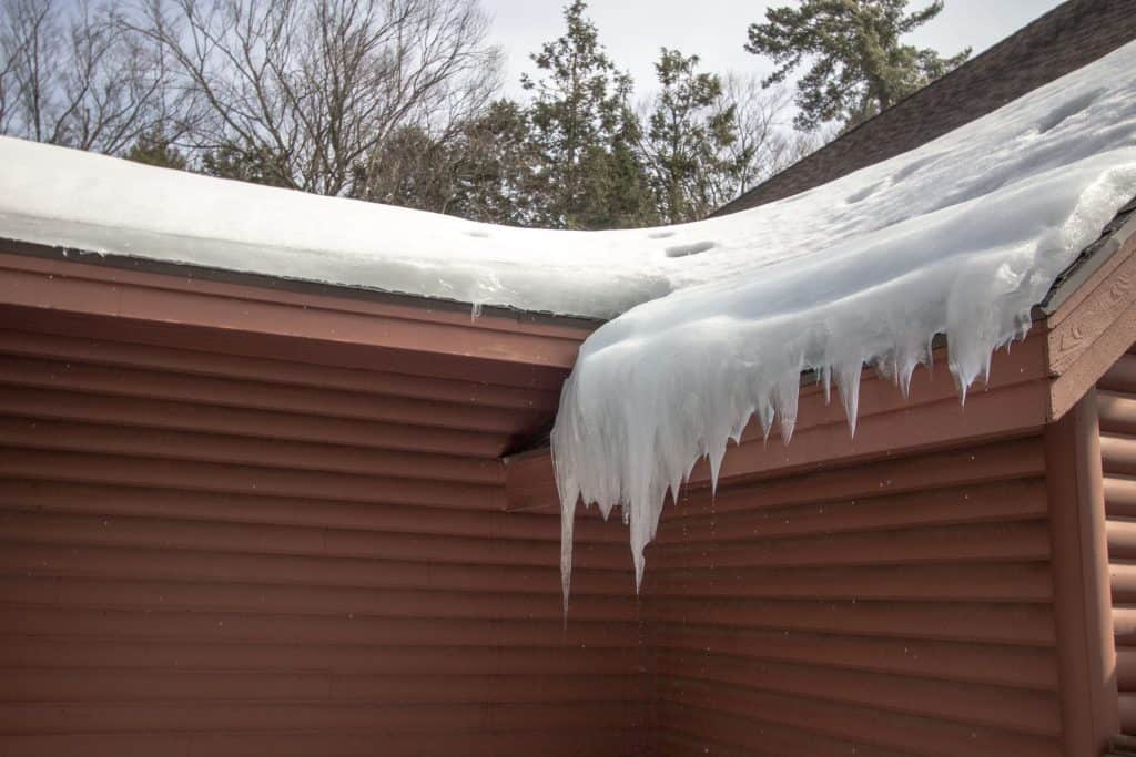 Ice Dam On Roof. Shingle roof on home with icicles and ice dam starts a leak on the roof.
